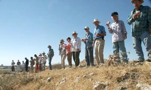 Part of the `Umayri-2002 excavation team, lined up along the northern edge of the tell, following the inaugural slaughter of the watermelon at second breakfast on our first day. Photo Larry Murrin)