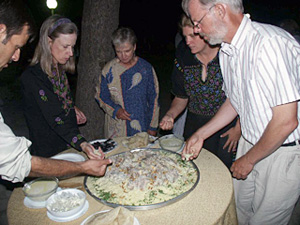 Hungry Group Gathers around One of Several Platters Piled High with Rice, Pine Nuts, Goat Meat and Yoghurt Sauce