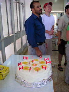 Mohammad Ahmuru, the cook, standing next to the cake he baked for Canada Day (photo by Katie Van Petten)