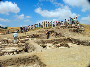 David Hopkins (standing left center), Field Supervisor of Field L, indicating new areas of excavation