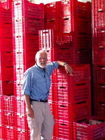 Doug Clark dwarfed by the stacks of red crates filled in the storeroom with supplies and equipment (photo courtesy Denise Herr)